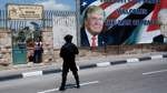 A soldier stands guard over the route as people watch Trump's motorcade carry him back to Jerusalem after his meeting with Abbas in the West Bank city of Bethlehem