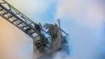 Auch die Feuerwehrleute auf der Drehleiter haben neben den Flammen mit dichtem Rauch zu kämpfen.