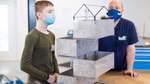 Ausbildungsleiter Markus Tönjes schaut bei Pit noch mal genauer hin. Selbst die Dachkonstruktion aus dem 3D-Drucker passt perfekt in den Kasten.